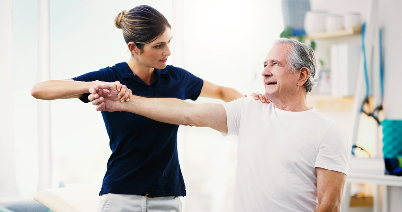 Physical Therapist helping patient with shoulder pain